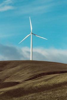 Foto vertical de uma turbina eólica em pastagem seca
