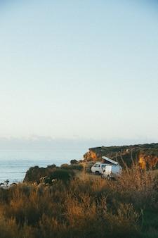 Foto vertical de uma van branca perto de um penhasco à beira-mar durante o dia
