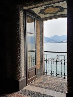 Foto vertical de uma varanda com vista para o mar e colinas