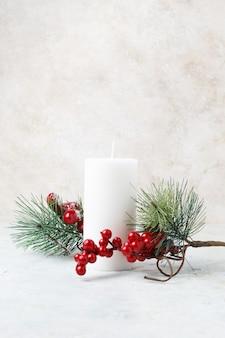 Foto vertical de uma vela branca cercada por azevinhos de natal e folhas em uma superfície de mármore branco