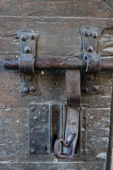 Foto vertical de uma velha fechadura de uma porta enferrujada e com a madeira velha. villefranche de conflent na frança