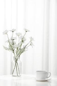 Foto vertical de uma xícara de café ao lado de um vaso cheio de lindas flores brancas, dentro de casa