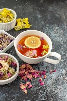 Foto vertical de uma xícara de chá de ervas perto de tigelas de flores secas em fundo cinza