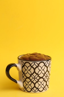 Foto vertical de uma xícara de chocolate quente isolada em um fundo amarelo