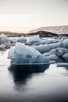 Foto vertical de vários pedaços de gelo na lagoa glacial jokulsarlon, na islândia