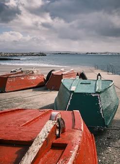 Foto vertical de velhos barcos invertidos vermelhos e verdes na costa sob um céu nublado
