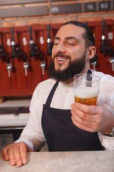 Foto vertical do barman barbudo feliz desfrutando do sabor da cerveja de sua cervejaria