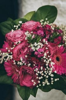 Foto vertical do buquê feito de lindas flores rosas e brancas
