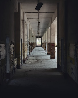 Foto vertical do corredor de um prédio abandonado à luz do dia
