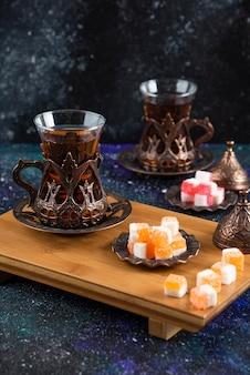 Foto vertical do jogo de chá com delícias turcas na tábua de madeira