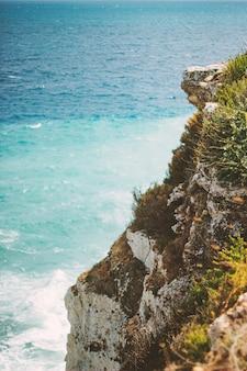 Foto vertical do oceano visto de um penhasco durante o dia
