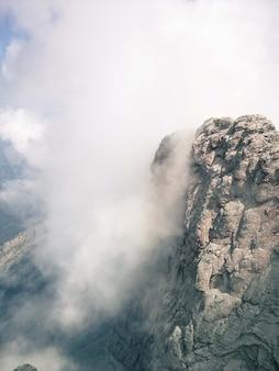 Foto vertical do penhasco em um dia de neblina - perfeita para o fundo