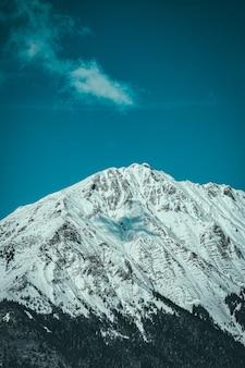 Foto vertical do pico da montanha coberto de neve