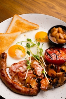 Foto vertical do saboroso café da manhã inglês em um restaurante sobre uma mesa de madeira
