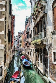 Foto vertical dos barcos no rio passando por edifícios e casas
