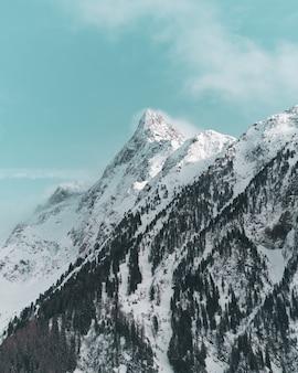 Foto vertical dos belos picos das montanhas cobertas de neve
