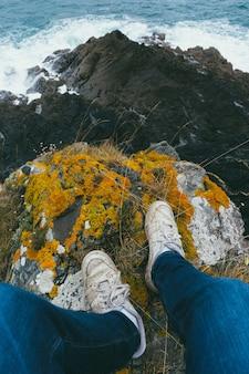 Foto vertical dos pés de uma pessoa no topo de um penhasco coberto de musgo