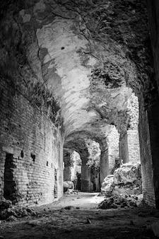 Foto vertical em escala de cinza das ruínas de um prédio antigo