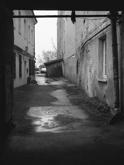 Foto vertical em escala de cinza de uma rua com edifícios antigos e água da chuva no solo