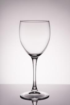 Foto vertical em tamanho grande de vidro de vinho transparente limpo com reflexos isolado na parede branco cinza com gradiente