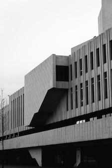 Foto vertical em tons de cinza da fachada de um edifício moderno