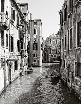 Foto vertical em tons de cinza de um canal no distrito histórico de veneza, itália