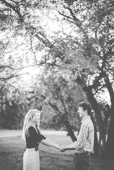 Foto vertical em tons de cinza de um casal cristão de mãos dadas no parque