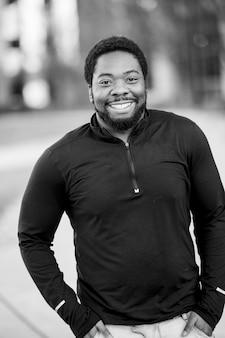 Foto vertical em tons de cinza de um homem afro-americano atraente sorrindo