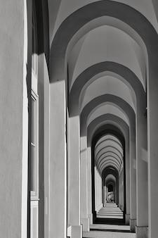 Foto vertical em tons de cinza de um longo corredor com várias colunas em forma de arco