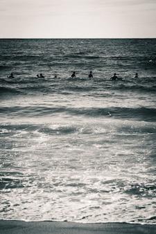 Foto vertical em tons de cinza de um mar com silhuetas de pessoas