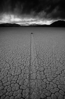 Foto vertical em tons de cinza de um terreno deserto de areia cercado por um cenário montanhoso