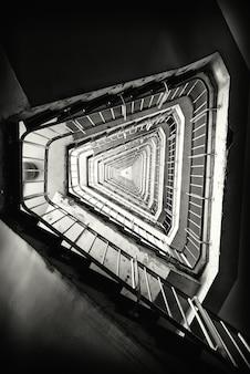 Foto vertical em tons de cinza de uma escada em um prédio
