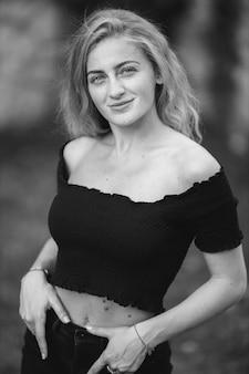 Foto vertical em tons de cinza de uma linda garota sorridente
