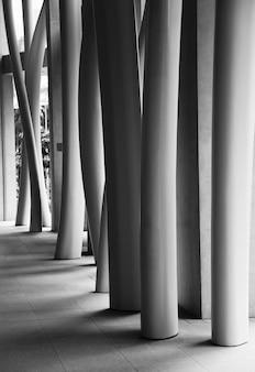 Foto vertical em tons de cinza do interior de um edifício moderno com colunas tortas