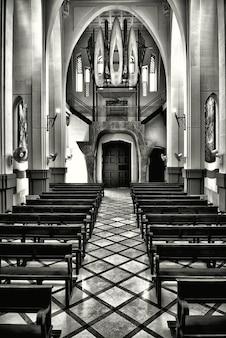Foto vertical em tons de cinza do interior de uma antiga igreja cristã histórica