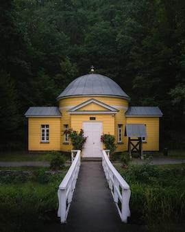 Foto vertical frontal de uma instalação cristã amarela com uma estrada estreita e um jardim em frente a uma floresta