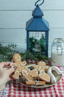 Foto vertical. mão feminina que tira o biscoito do prato.