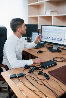 Foto vertical. o examinador de polígrafo trabalha no escritório com seu equipamento detector de mentiras