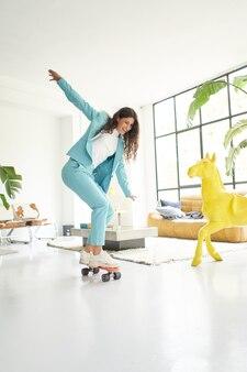 Foto vertical vertical de mulher de negócios andando de skate vestida com roupa de trabalhadora de escritório