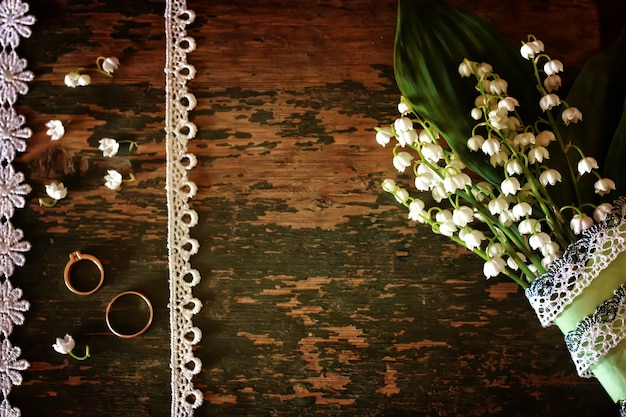 Foto vintage buquê de lírios do vale e anel de casamento