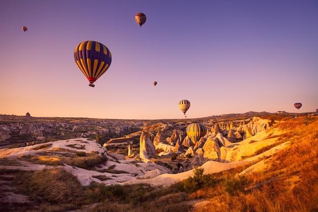 Foto vintage de balão de ar quente voando sobre paisagem rochosa