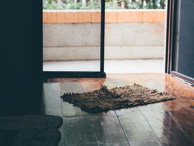 Foto vintage de capacho macio no antigo piso de madeira da porta da frente