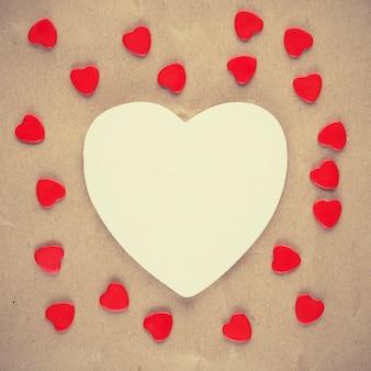 Foto vintage de coração branco e pequenos corações vermelhos em papel velho