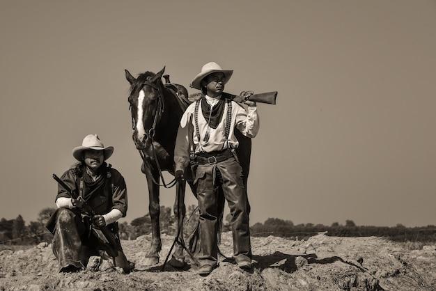 Foto vintage, de dois homens vestindo uma roupa de cowboy com um cavalo e uma arma na mão.