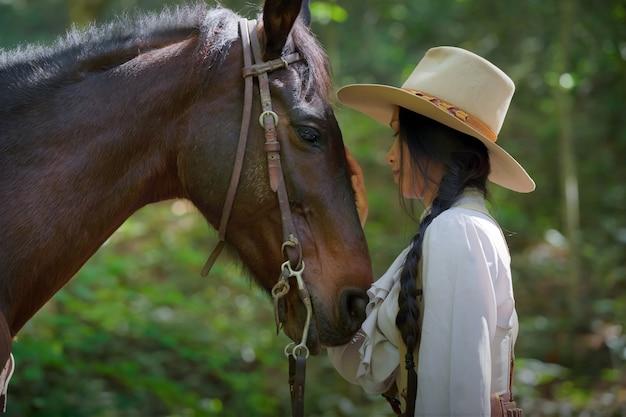 Foto vintage de uma cowgirl com um cavalo preto.