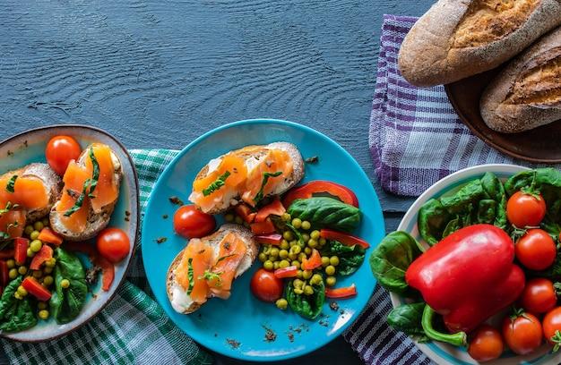 Fotocomposição sanduíche de café da manhã com salmão em uma vista superior do fundo de madeira