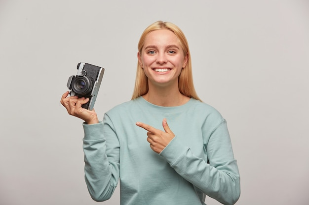 Fotógrafa adorável tirando uma sessão de fotos, inspirada na câmera fotográfica retro vintage na mão
