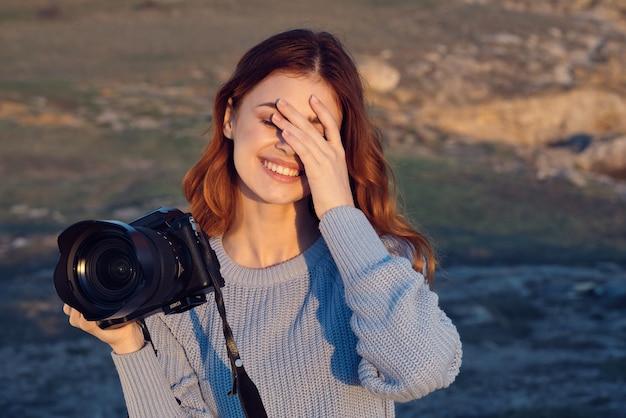 Fotógrafa alegre com uma câmera nas mãos sob o sol da natureza