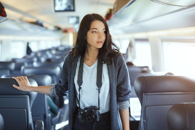 Fotógrafa atraente com câmera dslr em pé no trem e olhando para a câmera enquanto