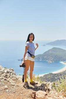 Fotógrafa caminha ao longo da trilha da via lícia. fethiye, oludeniz. linda vista para o mar e para a praia. caminhadas nas montanhas da turquia